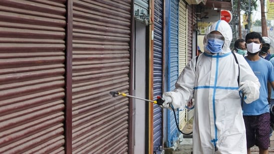 A man wearing protective gear sprays disinfectant after the government eased Covid-19 induced lockdown restrictions on June 6, 2021.