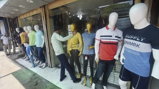 After further ease in the COVID-19 lockdown in the capital, a worker arranged mannequins outside a shop at the Karolbagh market on Monday morning.(PTI)