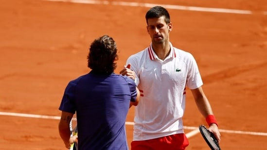 Italy's Lorenzo Musetti shakes hands with Serbia's Novak Djokovic after retiring injured from their fourth-round match.(REUTERS)