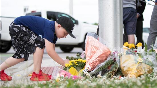 A young Londoner leaves a Hulk Action Figure for the nine year old boy who remains in hospital with serious injuries, at the scene where a man driving a pickup truck struck and killed four members of a Muslim family in London, Ontario, Canada on June 7, 2021.(AFP Photo)