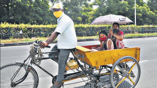 A family using an umbrella and cap to shield themselves from the scorching sun in Chandigarh on Monday. (Ravi Kumar/HT)