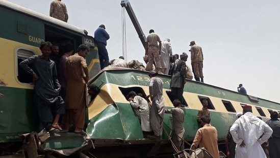 Security personnel and onlookers stand at the site of a train accident in Daharki area of the northern Sindh province on June 7, 2021 (AFP).