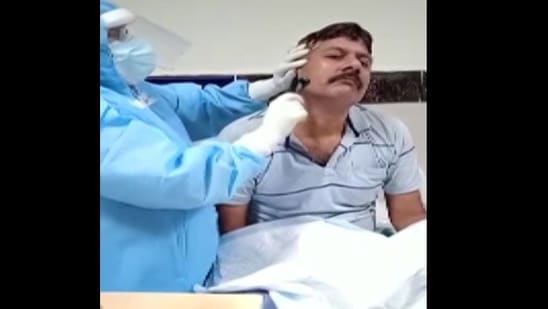 The image shows a healthcare worker shaving the beard of a Covid patient in Odisha.(ANI)