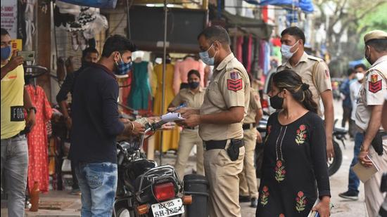 A Delhi Police personnel issues challan to a shopkeeper for not ensuring social distancing at his shop in Sarojini Nagar market in New Delhi on Tuesday, June 8. (Raj K Raj / HT photo)