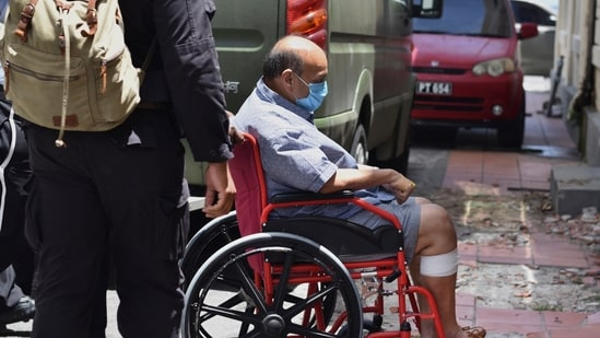 Antigua and Barbuda businessman Mehul Choksi is taken in a wheelchair to the magistrate's court by police after his arrest for illegal entry into the country, in Roseau, Dominica, Friday, June 4, 2021. (AP)