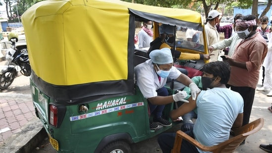Health workers administer Covid-19 vaccine doses to auto-rickshaw drivers outside the railway station in Ranchi. (PTI Photo)