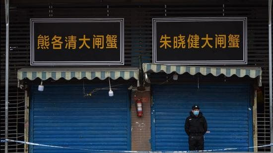 In this file photo taken on January 24, 2020, a security guard stands outside the Huanan Seafood Wholesale Market where the coronavirus was detected in Wuhan, China. (AFP)