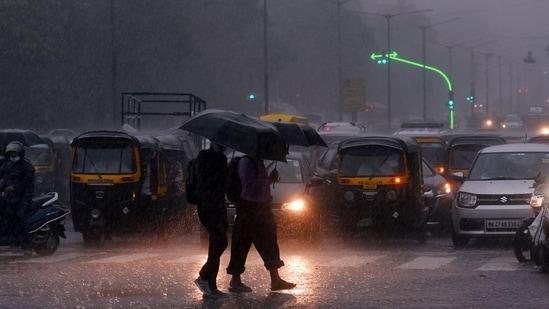 Commuters make their way during heavy rain, near Oberoi Mall at Goregaon Mumbai on June 9, 2021.