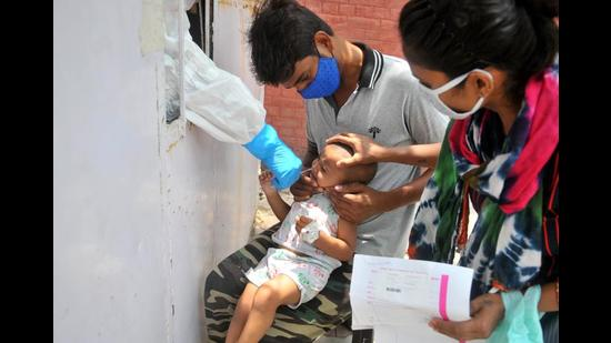 A health worker testing a child for Covid-19 at the Sector 45 Civil Hospital in Chandigarh on Thursday. (Ravi Kumar/HT)
