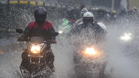 indiaCommuters make their way through the waterlogged road during heavy rain, at Kings Circle, in Mumbai, on June 9 (PTI)