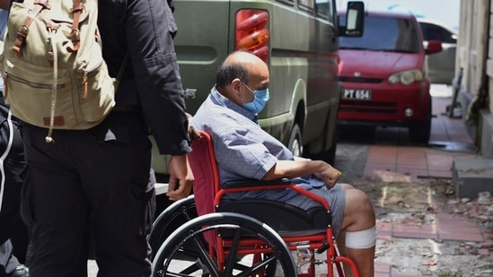 Mehul Choksi is taken in a wheelchair to the magistrate's court by police after his arrest for illegal entry into Dominica, in Roseau on June 4.(AP Photo)