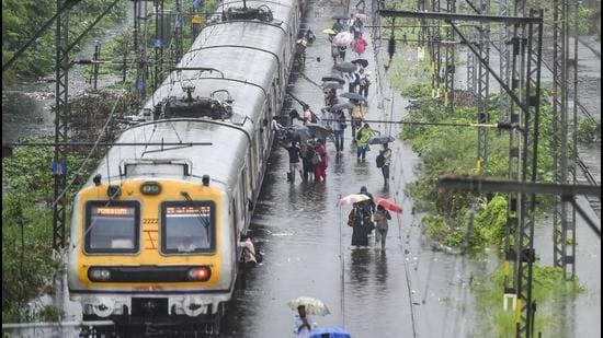 Stranded local train commuters walk on the waterlogged railway tracks during rain, at Kurla in Mumbai on Wednesday, June 9. (PTI)