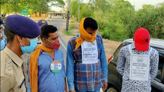Police personnel stick posters saying 'Mind the Gap' with the danger sign on people who are not inoculated yet under 'Roko Toko Campaign', in Niwari on Wednesday, June 9. (ANI)