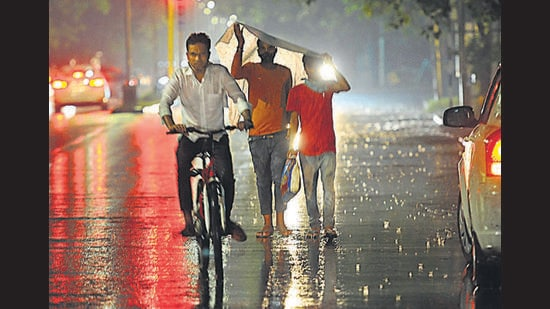 A cyclist and pedestrians caught in the showers that lashed Chandigarh on Thursday evening. According to the weather department, rain is likely on Friday as well. (Keshav Singh/HT)