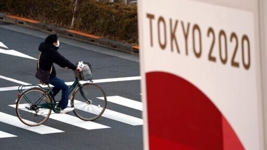 FILE - Man wearing a protective mask to help curb the spread of the coronavirus rides a bicycle near a banner of the Tokyo 2020 Olympics in Tokyo.(AP)