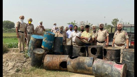 Police and excise officials with the seized drums at Shakri village of Patti sub-division on Thursday.