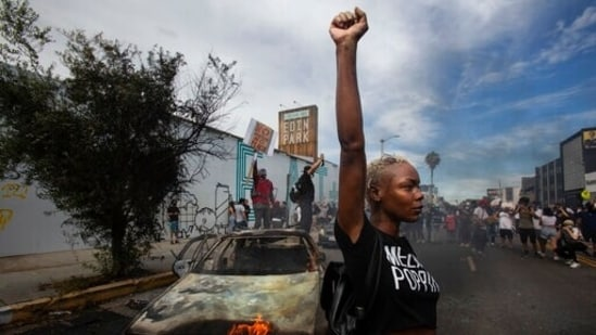 A protester raises her fist in the air next to a burning police vehicle in Los Angeles during a demonstration over the death of George Floyd. (AP)