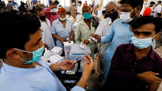 Residents with their registration cards gather at a counter to receive a dose of the coronavirus disease (Covid-19) vaccine at a vaccination center in Karachi, Pakistan June 9, 2021. (REUTERS/Akhtar Soomro)