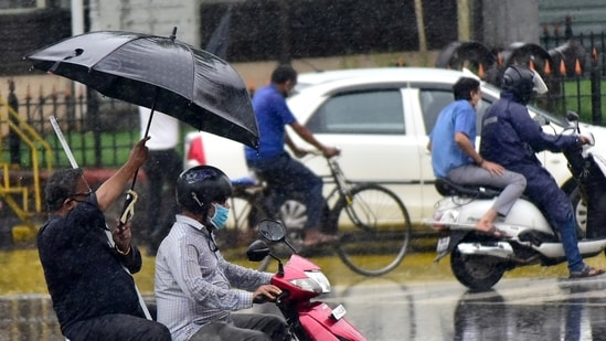 A pillion rider covers the rider from rain by holding the umbrella at CSMT, in Mumbai.