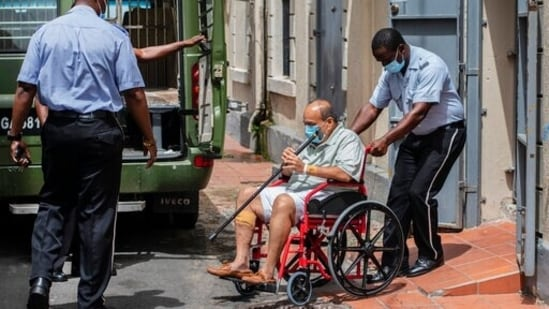 Antigua and Barbuda businessman Mehul Choksi is taken to a police van via a wheelchair by a police officer after attending a court hearing, in Roseau, Dominica.(AP)