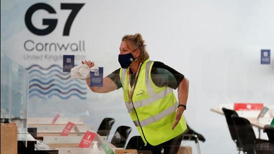 A woman cleans anti-coronavirus disease (Covid-19) screens on desks at a media centre inside the National Maritime Museum, as preparations are underway for the G7 leaders summit, Falmouth, Cornwall, Britain. (REUTERS)