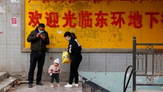 A family stands at the entrance to an underground retail street in Aksu in western China's Xinjiang Uyghur Autonomous Region.(AP)