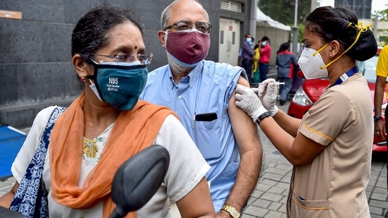 A health worker administers a dose of the Covid-19 vaccine to a person at a drive-in vaccination centre, at MGM Hospital, in Chennai.(PTI)