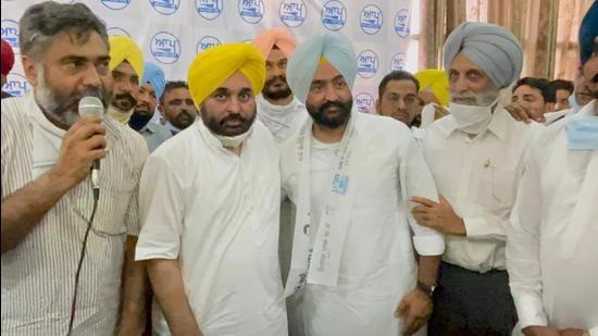 AAP Punjab president Bhagwant Mann with Youth Congress leader Davinderjeet Singh Laddi (blue turban) and others in Moga on Friday. Laddi was considered close to Punjab finance minister Manpreet Singh. (HT photo)