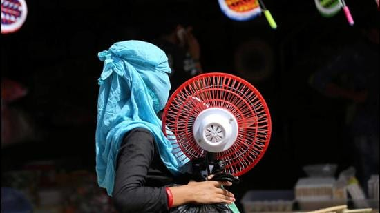 A woman carries a table fan on a hot summer day in Jammu on Friday. (PTI)