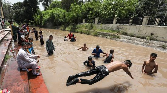 People take bath in the Ranbir Canal on a hot summer day in Jammu on Wednesday, June 9. (File photo)