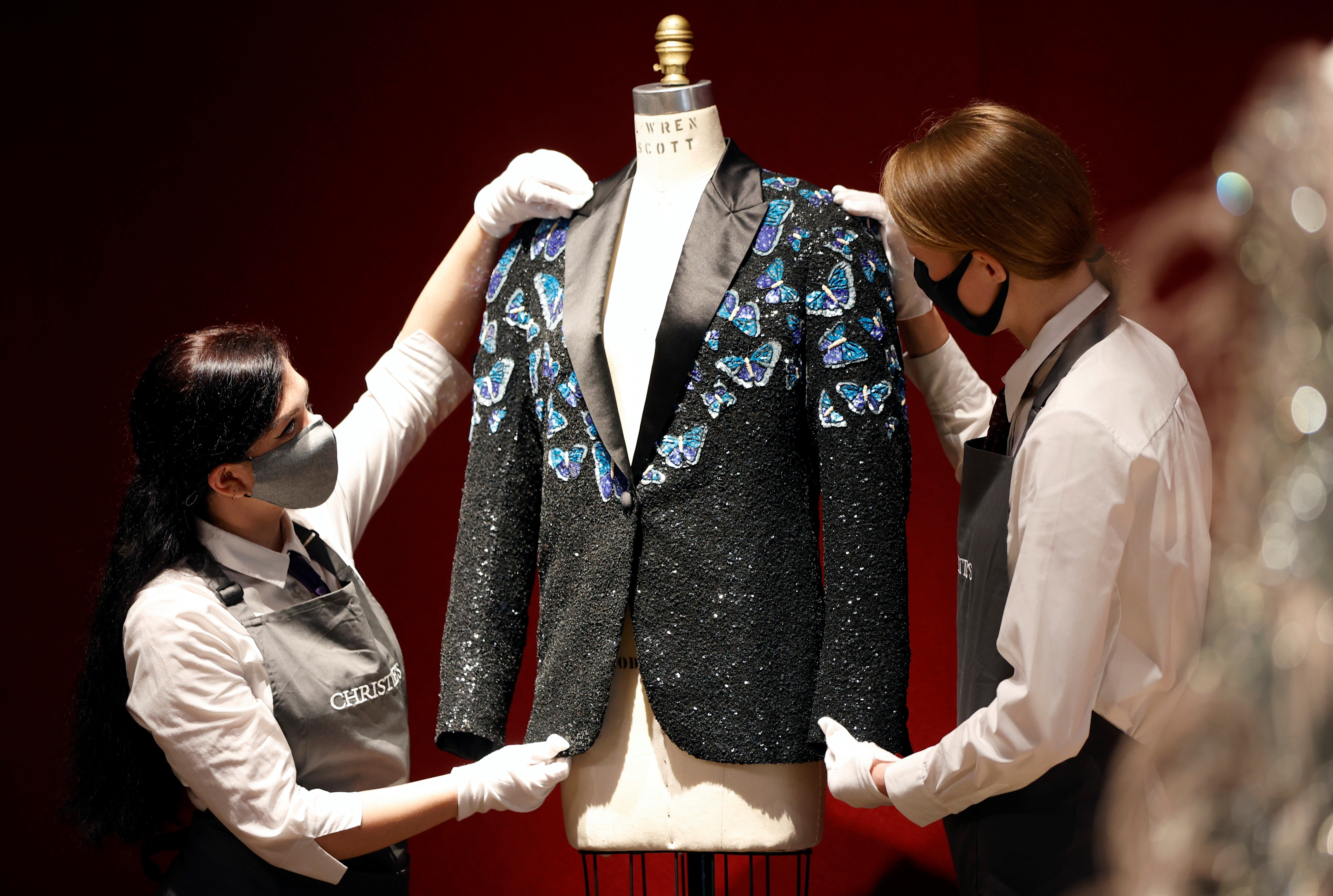 Gallery assistants pose for a photograph with the Butterfly jacket designed for Mick Jagger by designer L'Wren Scott at Christie's in London, Britain, June 10, 2021. (REUTERS)