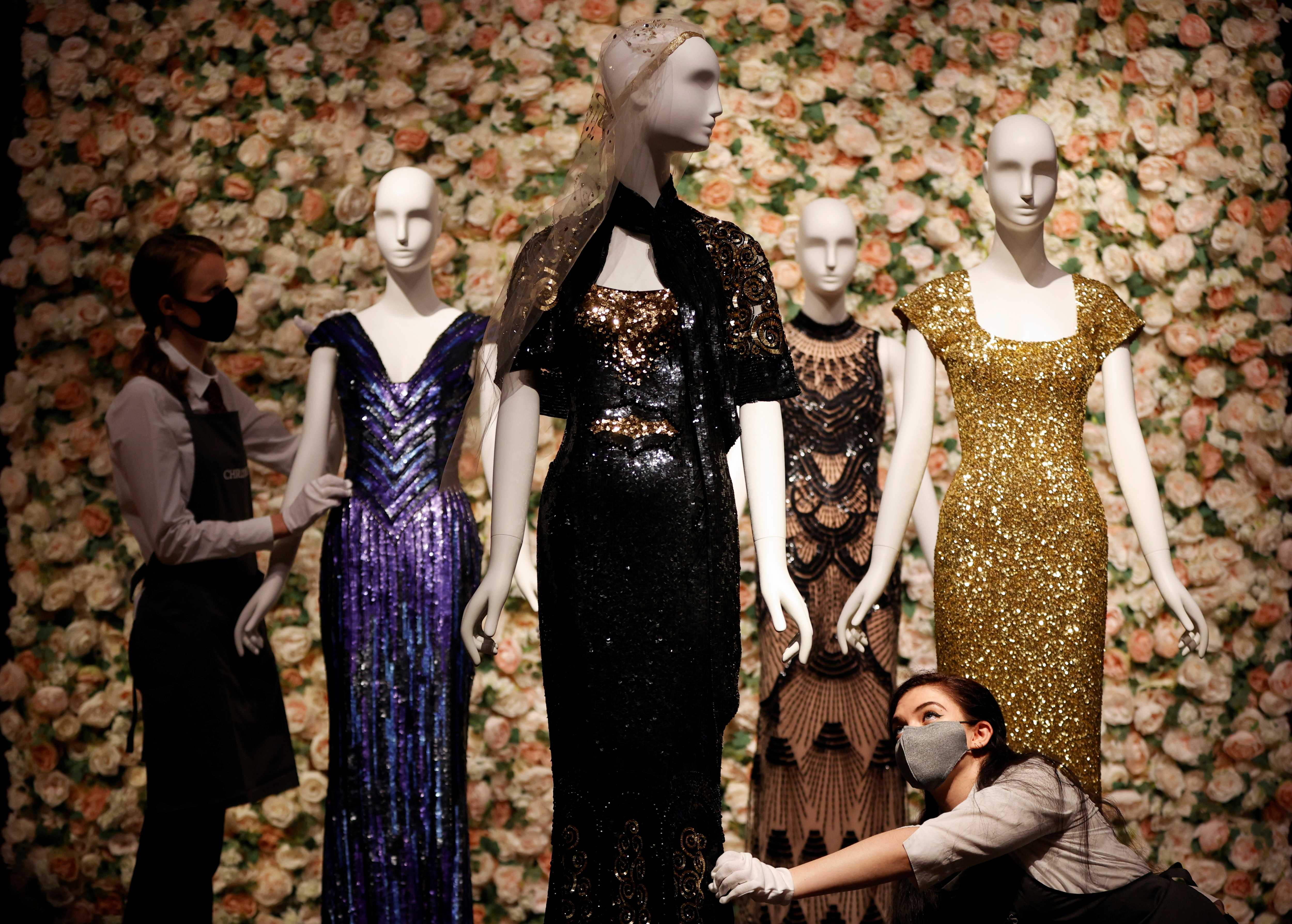 Gallery assistants pose for a photograph next to a black and gold 'Oscar' dress worn by Nicole Kidman by designer L'Wren Scott at Christie's in London, Britain, June 10, 2021. (REUTERS)