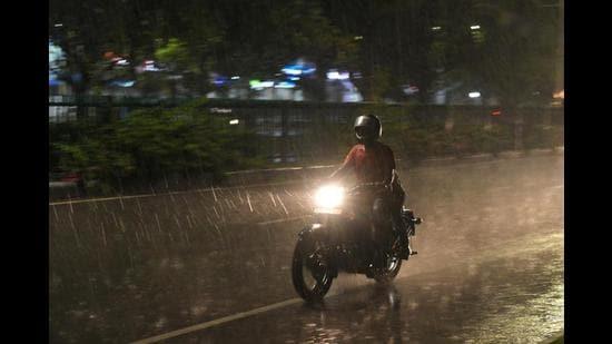 A motorist caught in the showers in Chandigarh on Thursday. (Ravi Kumar/HT)