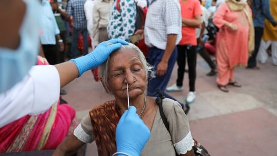 A devotee reacts as a health worker collects a swab sample, on the banks of the Ganges river during Kumbh Mela.(REUTERS)