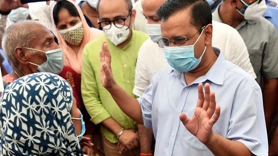 Delhi CM Arvind Kejriwal interacts with people during the 'Jahaan Vote Wahin Vaccine' drive organized by Delhi Government at a School, in New Delhi on Wednesday. (ANI Photo)