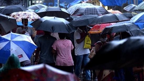 Crowd of people under the sea of umbrellas at Koparkhairane Market walk in rain in Navi Mumbai.