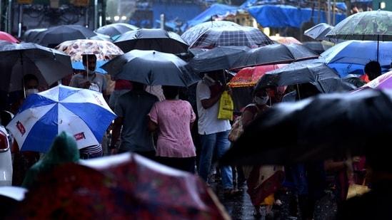 Crowd of people under the sea of umbrellas at Koparkhairane Market walk in rain in Navi Mumbai. (Bachchan Kumar/HT Photo)