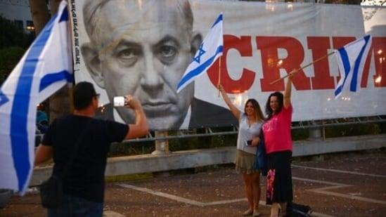 Israelis pose in front of a poster showing outgoing Israeli prime minister Benjamin Netanyahu in Tel Aviv, Israel.(AP)
