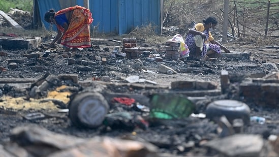 Rohingya refugees look for their belongings amid the charred remains of their camp following a fire incident that broke out earlier today in New Delhi.(AFP)