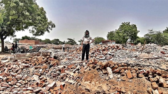 A man stands on the rubble of demolished houses in Jewar's Nagla Ganeshi, one of the seven villages that have been acquired for construction of an international airport. (HT Photo)