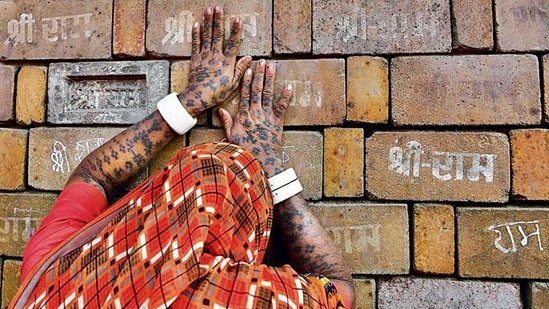 A devotee prays to the bricks expected to be used in construction of the Ram temple, in Ayodhya on November 11, 2019. (AP)