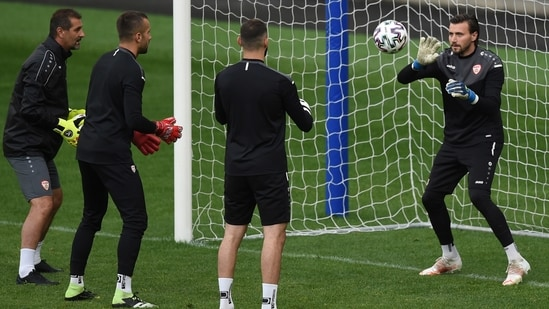 North Macedonia's goalkeeper Stole Dimitrievski (R) catches the ball during a training session at the Steaua stadium in Bucharest(AP)
