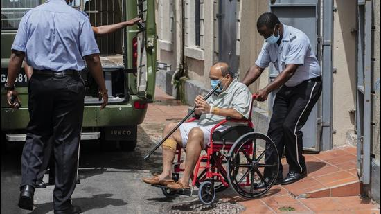 Mehul Choksi is taken to a police van via a wheelchair by a police officer after attending a court hearing, in Roseau, Dominica, Thursday, June 10. (File photo)