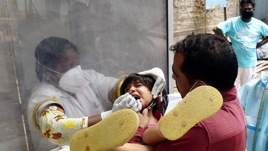 A healthcare worker testing a child for Covid-19 (ANI)