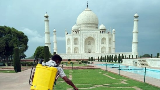 A worker spray disinfects at Taj Mahal premises in Agra on Monday, a day before its reopening.(ANI Photo)