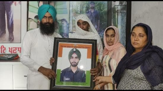 Gurbinder Singh's family with his photo at their home in Tolowal village near Sunam in Sangrur. (HT Photo)