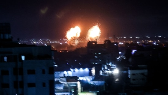 Explosions light-up the night sky above buildings in Gaza City as Israeli forces shell the Palestinian enclave.(AFP)