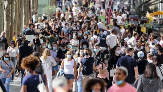 People wearing face masks walk on the Champs Elysees Avenue in Paris in this file photo from August 2020. (AFP)