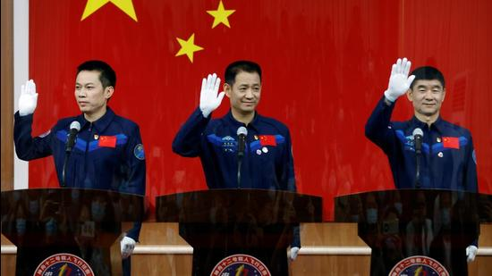 Astronauts Nie Haisheng, Liu Boming and Tang Hongbo wave as they meet members of the media behind a glass wall before the Shenzhou-12 mission to build China's space station, at Jiuquan Satellite Launch Center near Jiuquan, Gansu province. (REUTERS)