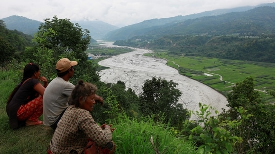People from a hilltop view the swollen Melamchi river in Sindhupalchok, on June 16. The flash floods in Sindhupalchok district, which touches Tibet on the Northern side, are suspected to be triggered by a glacial outburst that has dumped a large mass of mud, stones and residues in the Melamchi Corridor.(Navesh Chitrakar / REUTERS)